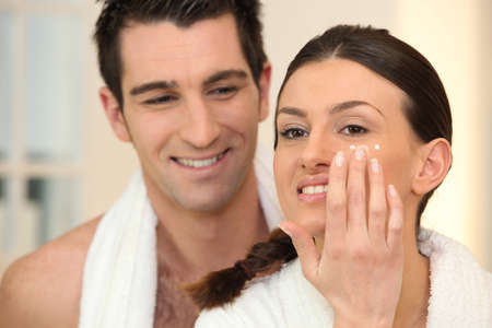 couple bathroom: Woman applying under eye cream Stock Photo