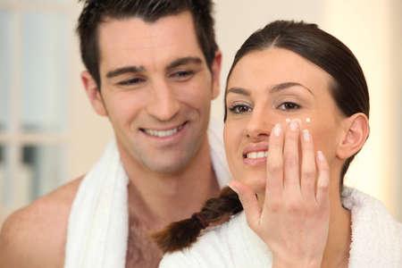 bathroom women: Woman applying under eye cream Stock Photo