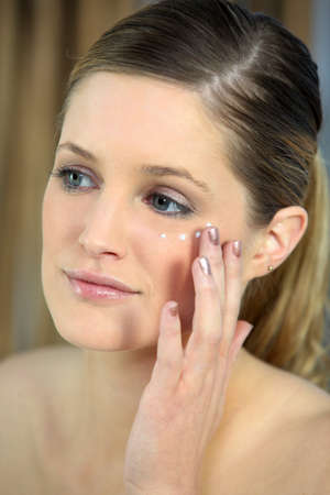Pretty woman applying under-eye cream photo