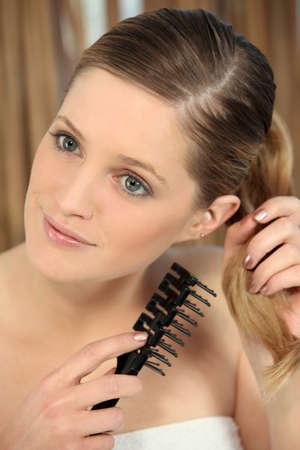 untangle: Pretty young woman untangling her hair