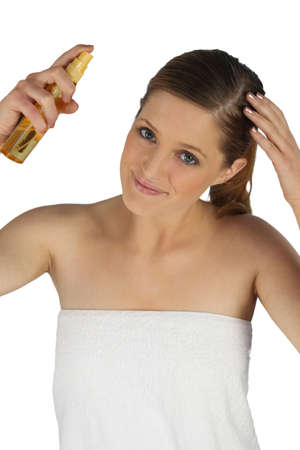 condicionador: Woman spraying conditioner into her hair