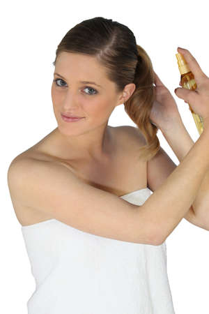 hair product: Blond woman using hair spray
