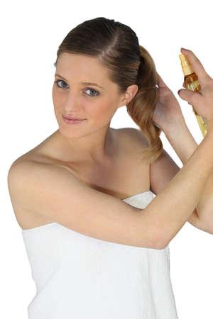 productos quimicos: Mujer rubia con spray para el cabello Foto de archivo