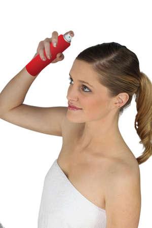 hairspray: Young woman using hairspray