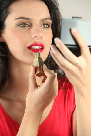 Woman applying make-up photo
