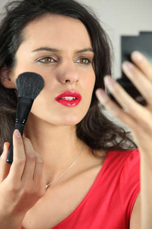 beautiful woman putting on some make up photo