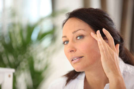 rejuvenate: a woman spreading out cosmetic cream on her face Stock Photo
