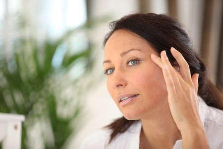 mirar espejo: una mujer extendiendo crema cosm�tica en su rostro
