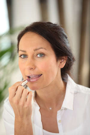 Brunette applying lipstick photo