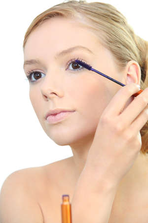 Woman applying mascara photo