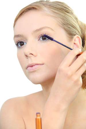 bare skinned: Woman applying mascara Stock Photo