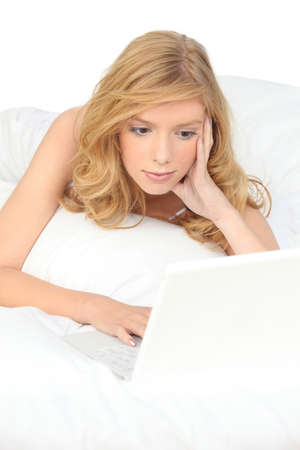 Woman with computer in bed Stock Photo - 13875781