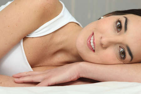 bellyache: Smiling girl lying on a bed