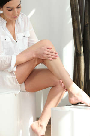 Woman feeling her legs photo