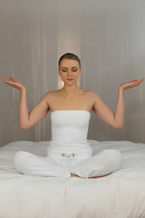 Woman meditating in her bedroom photo