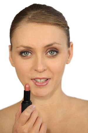 Woman putting on lipstick photo