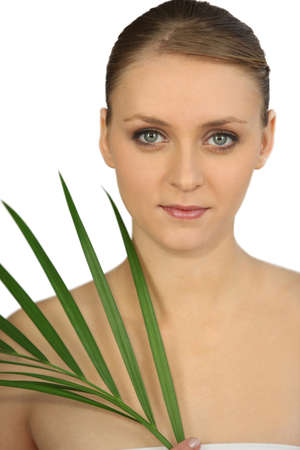pureness: bust shot of graceful blue-eyed blonde and plant Stock Photo
