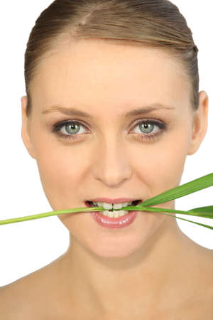 Woman holding a stem in between her teeth photo