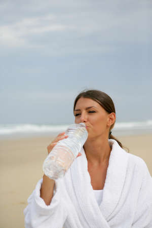 Woman drinking a bottle of water photo