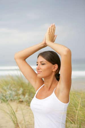 Woman doing yoga at the beach photo