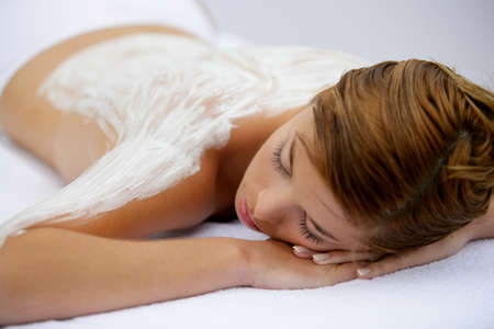 Young woman laid with cream on her back Stock Photo - 13875595