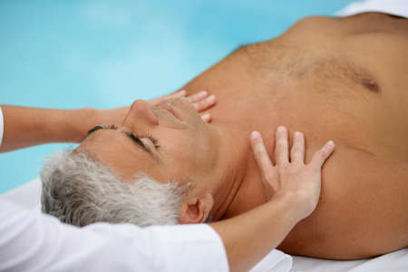 Mature man being massaged next to a swimming pool Stock Photo - 13875603