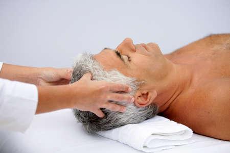 homme massage: homme d'âge mûr ayant un massage du cuir chevelu Banque d'images