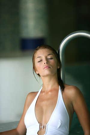 halter neck: Jonge vrouw in een witte halster-hals badpak loungen met een zwembad Stockfoto