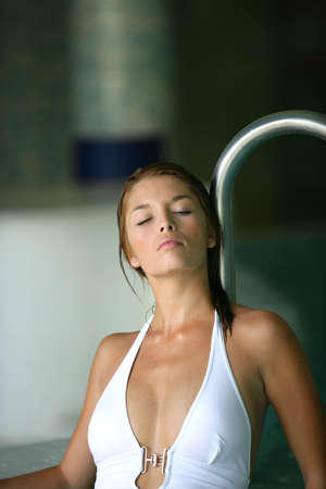 halterneck: Young woman in a white halter-neck swimsuit lounging by a pool