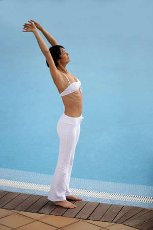 Woman stretching by a pool photo