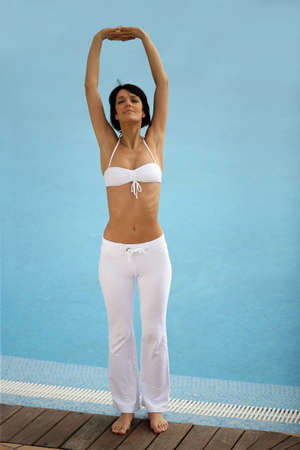 wet bikini: Woman stretching at a poolside