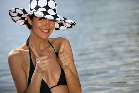 Thumbs up from a woman on the beach photo