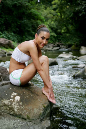 Attractive woman sat on a rock next to stream Stock Photo - 13875333