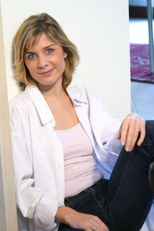 Portrait of a woman sitting on the floor and leaning against a wall photo