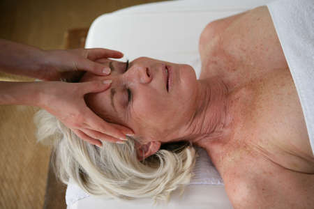 healthy seniors: senior woman having a massage in a spa center