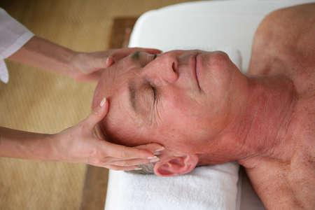 sensual massage: Man receiving a head massage Stock Photo