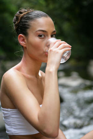 Woman drinking water by a brook photo