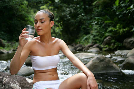 Brunette sat on rock with glass of water photo