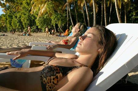 Friends sunbathing on a beach photo