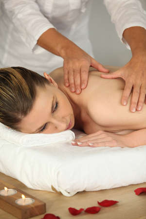 muscle tension: Woman receiving a back massage Stock Photo