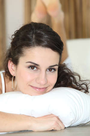 Pretty woman resting on a white pillow photo