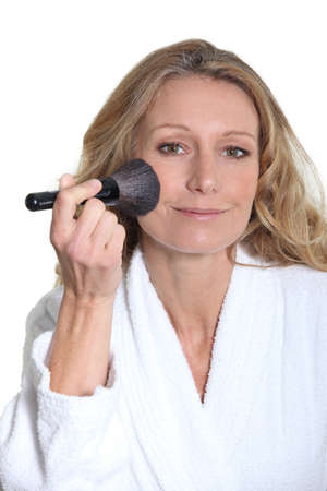 Woman in bathrobe using blusher brush photo