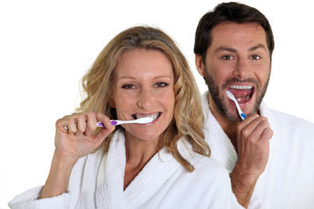 Couple in bathrobes cleaning teeth Stock Photo - 13867033