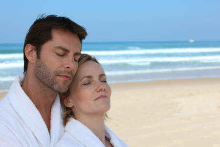 wife of bath: Husband and wife on the beach in bath robes Stock Photo