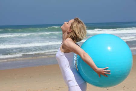 Exercises with blue ball on the beach photo
