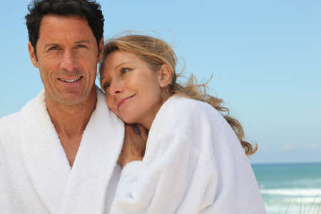couple in bathrobes on the beach photo