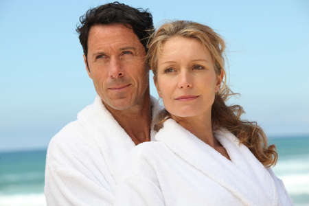 40s adult: Couple on the beach in white dressing downs