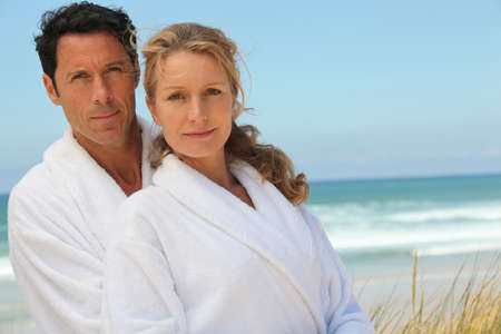 Husband and wife on the beach in bath robes Stock Photo - 13876452