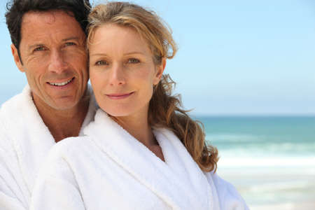 toweling: Couple in bathrobes on the beach Stock Photo