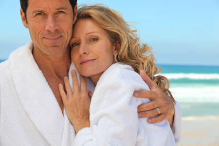 dressing gowns: A couple wearing dressing gowns and smiling at us.